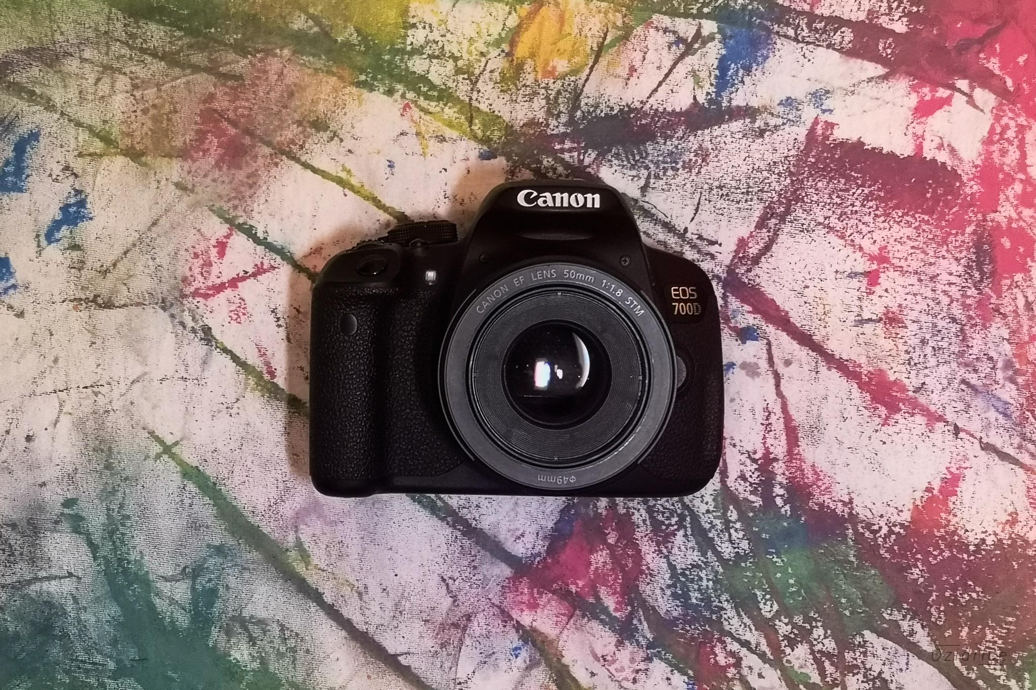 Appareil photo numérique de marque Canon sur un fond coloré