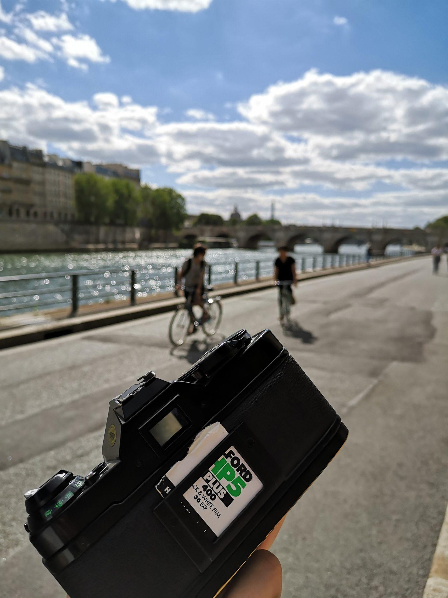 Photographie avec au premier plan un appareil photo argentique Canon AE1 Program, et au second plan les quais de Seine à Paris