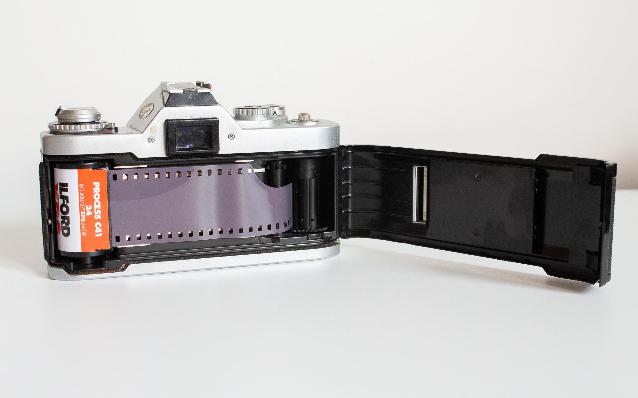 Photographie d'un Canon AV1, le dos ouvert, avec une pellicule Ilford Super XP2 chargée